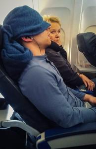 un homme dort dans l'avion avec une couverture sur la tête
