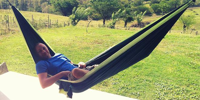 Geoffrey prend un peu de repos allongé dans un hamac sur la terrasse de sa maison en Martinique