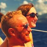 marion et geoffrey, un jeune couple qui vit en martinique, se trouvent sur le pont d'un voilier et sourient face à la mer des caraïbes