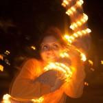 sharon entoure un palmier avec les bras, celui ci est recouvert d'une guirlande lumineuse et la photo est floue