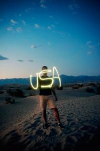 David est debout dans le sable de Mesquite Dunes dans la Vallée de la Mort (Death Valley) et il écrit le mot USA avec un briquet (appareil photo en pose longue) au coucher du soleil