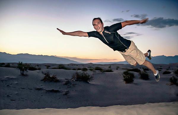 David imite superman en plongeant sur le sable de mesquite Dunes, dans la vallée de la mort aux états-unis à la tombée de la nuit