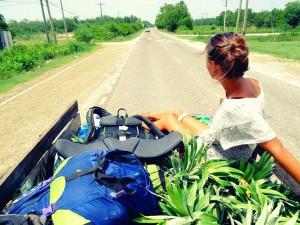 Jeanne est assise dans une petite carriole qui transporte des ananas, sur une route de Belize, en Amérique centrale