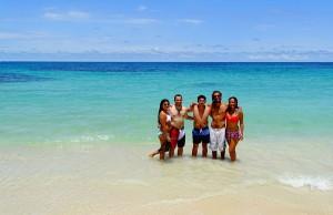 Jeanne et Stefenn sont avec des amis, les pieds dans l'eau, sur une plage de sable blanc du Panama en Amérique Latine