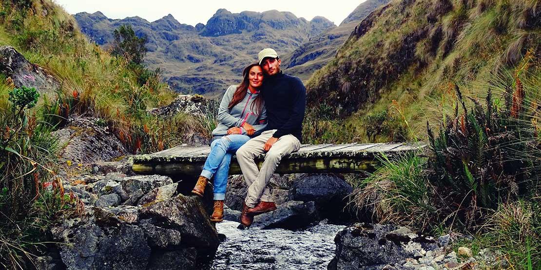 Jeanne et Stefenn sont assis sur un petit pont qui surplombe une rivière, laquelle serpente parmi les montagnes de l'Équateur, en Amérique du Sud