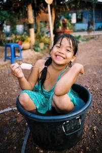 Fillette qui fête Songrkan dans une bassine d'eau