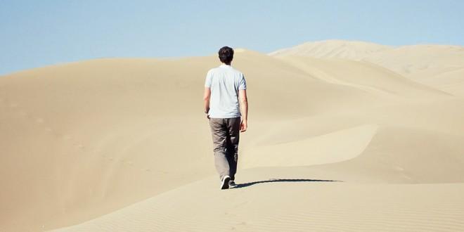 Homme de dos marchant dans le désert