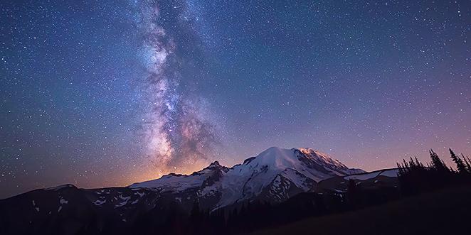 une montagne et un glacier sont photographiés de nuit en pose longue sous une véritable pluie d'étoiles et de galaxies